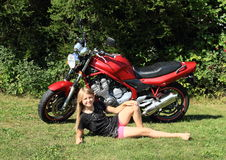 Girl lying in front of motorbike Royalty Free Stock Photos