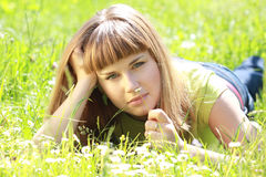 Girl lying in the garden and smelling a flower Royalty Free Stock Images
