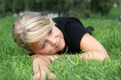 Girl lying in grass. A young girl relaxing on green grass Stock Photo