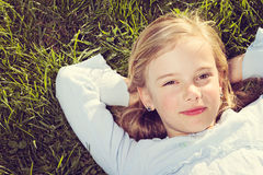 Girl lying in grass stock image