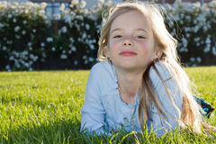 Girl lying in grass. A cute little girl lying down in the grass, backlit by the evening sun Royalty Free Stock Photo