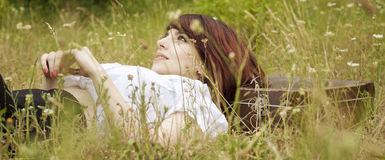 Girl lying in grass Stock Images