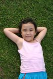 Girl lying on the grass. Girl wearing pink singlet lying on the grass Royalty Free Stock Image