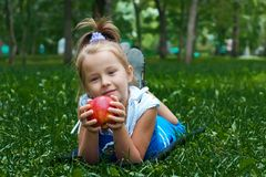 Girl lying on grass with Apple Stock Images