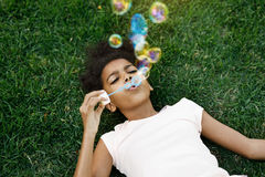 Girl lying on grass blowing bubbles Stock Images