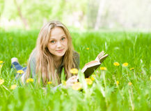 Girl lying on grass with dandelions reading a book and looking at camera Stock Image