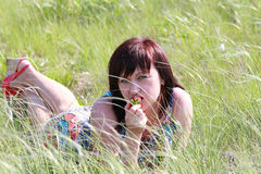 Girl lying in the grass and eating strawberries Royalty Free Stock Photo