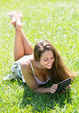 Girl lying on grass with ereader Stock Photo