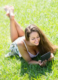 Girl lying on grass with ereader Stock Images