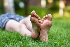Girl lying on the grass, feet on foreground. Girl lying on the grass, dirty feet on foreground Royalty Free Stock Images