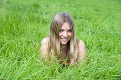 Girl lying on grass field Stock Image