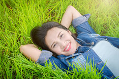 Girl lying on grass field and smiles Royalty Free Stock Photography