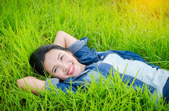 Girl lying on grass field and smiles Royalty Free Stock Image