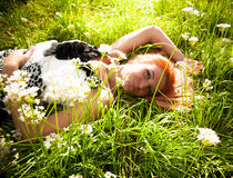 Girl lying on grass with flowers Stock Image