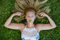 Girl lying on the grass. With a clover on her lips looking at camera stock photography