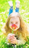 Girl lying on grass, grassplot on background. Child enjoy spring sunny day while lying at meadow with flowers. Girl on stock image
