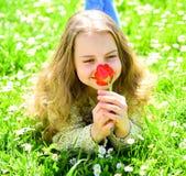 Girl lying on grass, grassplot on background. Girl on smiling face holds red tulip flower, enjoy aroma. Tulip fragrance. Concept. Child enjoy spring sunny day Royalty Free Stock Photos
