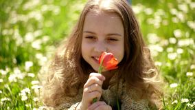 Girl lying on grass, grassplot on background. Tulip fragrance concept. Girl on smiling face holds red tulip flower stock video footage