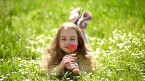 Girl lying on grass, grassplot on background. Tulip fragrance concept. Girl on smiling face holds red tulip flower stock video