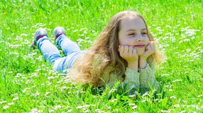 Girl lying on grass at grassplot, green background. Child enjoy spring sunny weather while lying at meadow. Springtime. Concept. Girl on smiling face spend stock photos