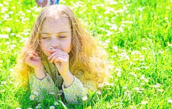 Girl lying on grass at grassplot, green background. Girl on dreamy face spend leisure outdoors. Child enjoy spring sunny stock images