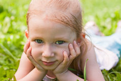Girl lying on grass,  hands on chin Stock Photo