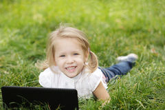 Girl lying on the grass with laptop Royalty Free Stock Photography