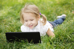 Girl lying on the grass with laptop Royalty Free Stock Photos