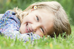 Girl lying on grass laughing Royalty Free Stock Images