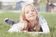 Girl lying in grass stock photo