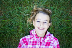 Girl lying on grass looking at camera royalty free stock image
