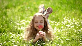 Girl lying on grass, nature on background, defocused. Child enjoy spring sunny day while lying at meadow. Girl on stock video footage