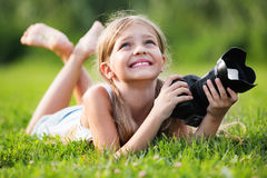 Girl lying on  grass with professional camera in hands Royalty Free Stock Images
