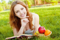 Girl lying on the grass and reading Royalty Free Stock Photo