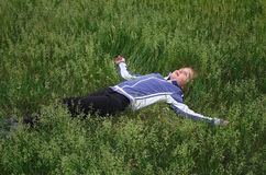 The girl lying in the grass. Girl resting in the green grass in the summer Royalty Free Stock Images