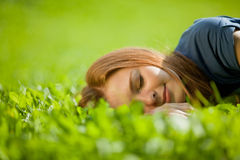 Girl lying on the grass and sleeping peacefully Stock Image