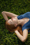 Girl lying on the grass and sleeping peacefully Stock Photo