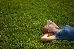 Girl lying on the grass and sleeping peacefully Stock Photography