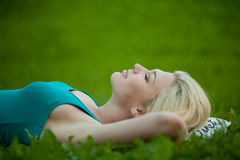Girl lying on the grass and sleeping peacefully Stock Images