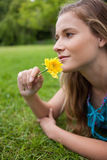 Girl lying on the grass while smelling a flower Stock Images