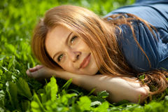 Girl lying on the grass and smiling Royalty Free Stock Image