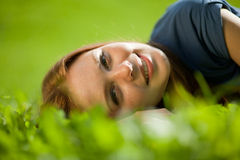 Girl lying on the grass and smiling Stock Photography