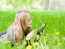 Girl lying on grass with tablet computer Royalty Free Stock Images
