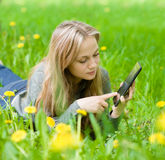 Girl lying on grass with tablet computer Stock Images