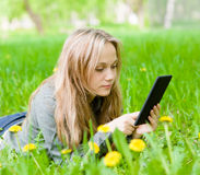Girl lying on grass with tablet computer Stock Photos