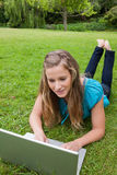 Girl lying on the grass while using her laptop. Young girl lying on the grass in the countryside with legs raised while using her laptop Royalty Free Stock Image