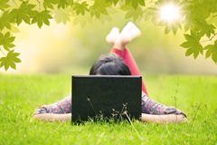 Girl lying on grass using laptop outdoor Royalty Free Stock Photos