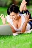 Girl lying on the grass works at the computer Stock Images