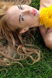 Girl lying on the grass with yellow flowers. Royalty Free Stock Photo