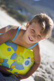 Girl (5-7) lying on green beach ball on sandy beach, smiling, close-up, portrait (tilt) Stock Photo